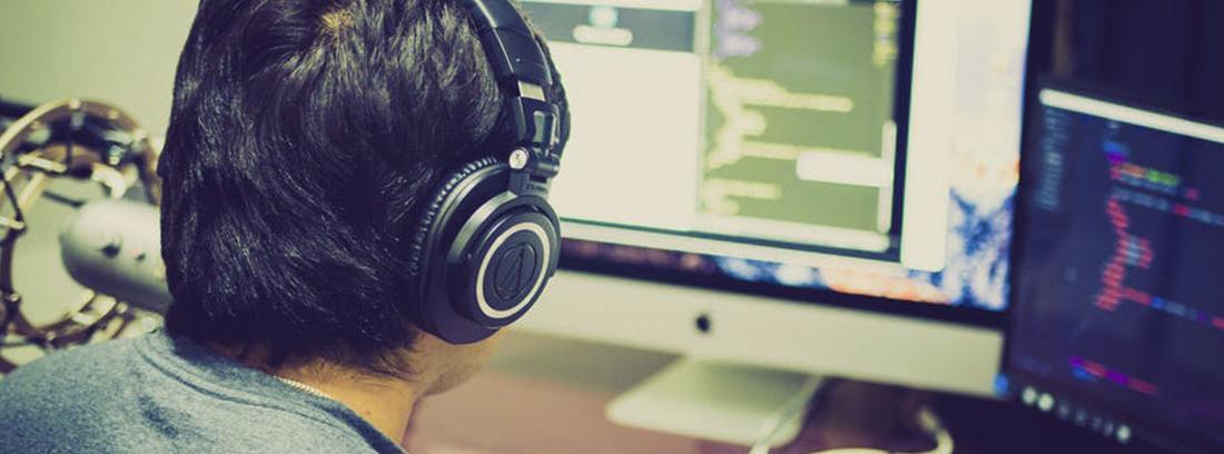 Persona con cascos grandes y negros delante de pantalla de ordenador sobre mesa