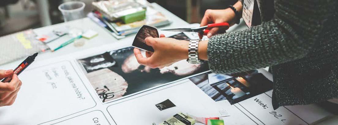 Manos sostienen foto y tijeras sobre una mesa llena de fotos y revistas