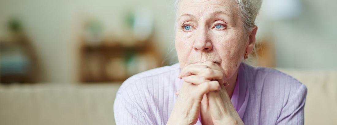 Mujer mayor en soledad mirando con pena