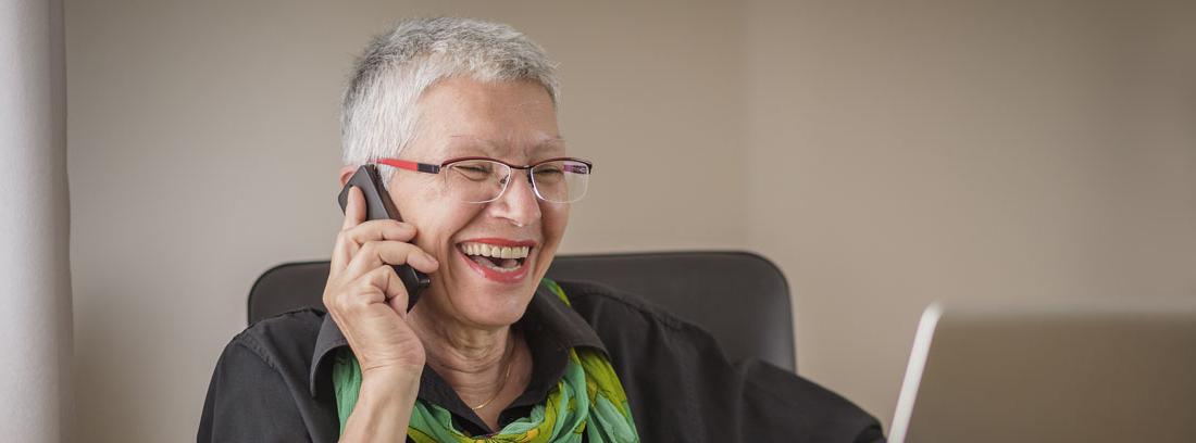Mujer sentada con pelo corto blanco con móvil en la mano y delante de portátil
