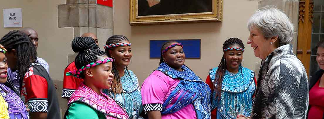 Grupo de mujeres con vestidos de colores junto a Theresa May con traje de chaqueta