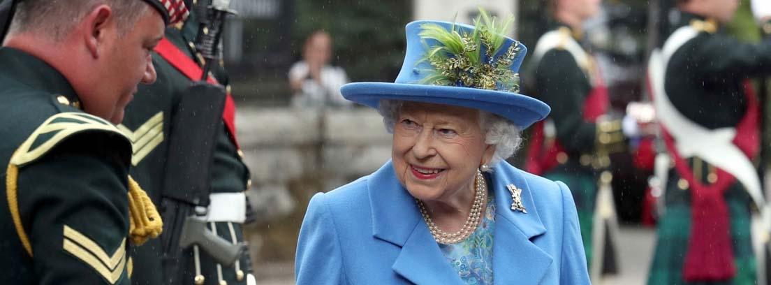 Reina Isabel II de Inglaterra con sombrero azul con hojas verdes y chaqueta azul