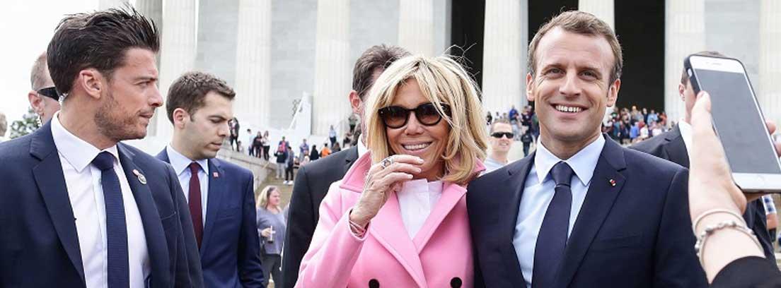 Brigitte Macron con gafas de sol y abrigo rosa junto a Emmanuel Macron
