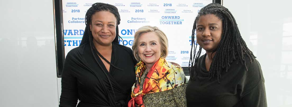 Hillary Clinton sonriente entre dos mujeres negras vestidas de negro