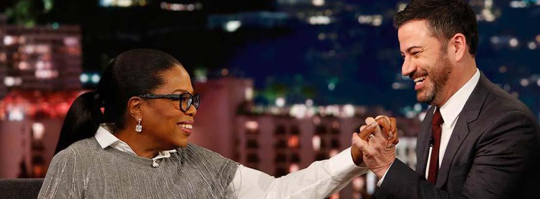Oprah Winfrey con gafas y camisa blanca tiende la mano a un joven sentado a su lado