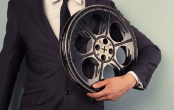 Hombre con traje sujetando una bobina de película
