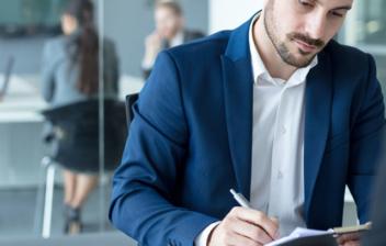 Hombre con traje firmando unos papeles, sentado junto a una mesa con una mujer enfrente
