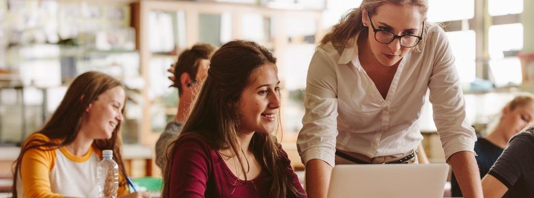 Una estudiante y una profesora en una clase llena de alumnos miran un ordenador