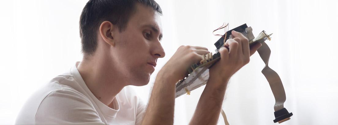 Un hombre arreglando la placa base de un ordenador