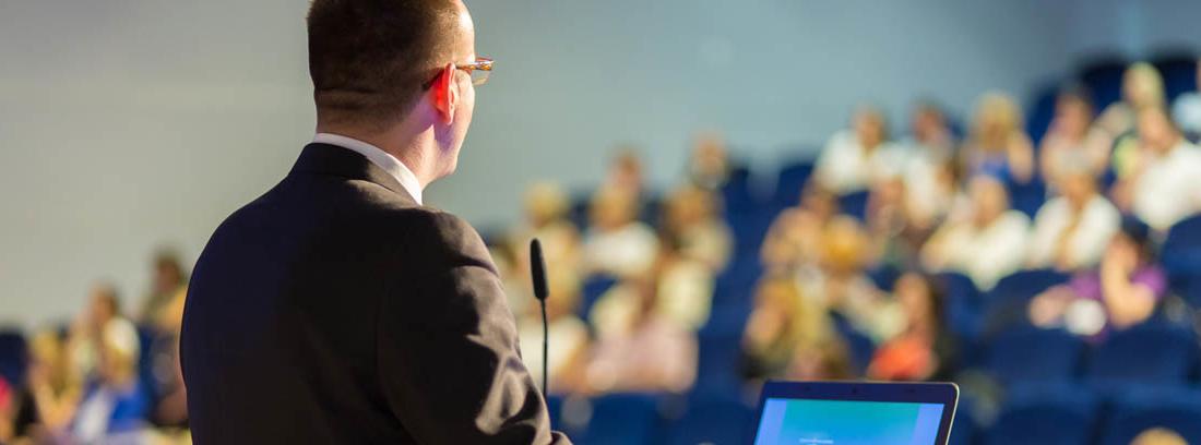 Hombre de espaldas con chaqueta oscura manos sobre un atril con micrófono