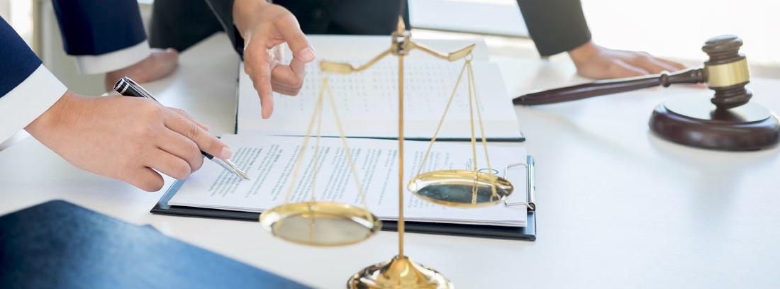 Sobre una mesa una balanza romana dorada, un mazo de madera, papeles y manos