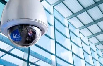 Cámara de seguridad redonda en un edificio acristalado