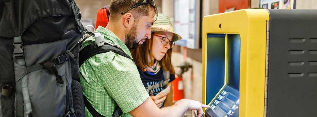 Hombre con gran mochila en la espalda y bolso delante de un cajero amarillo