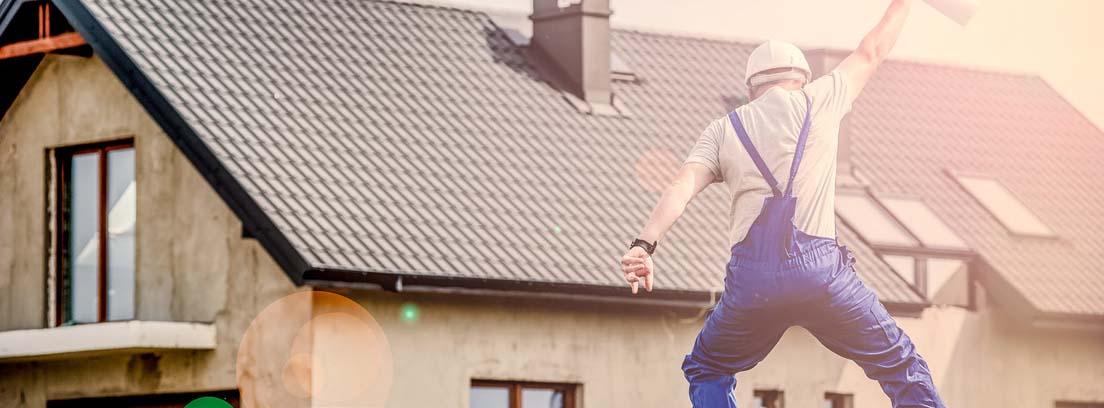 Hombre con mono azul, casco y rollo de papel en la mano en el aire delante de casa