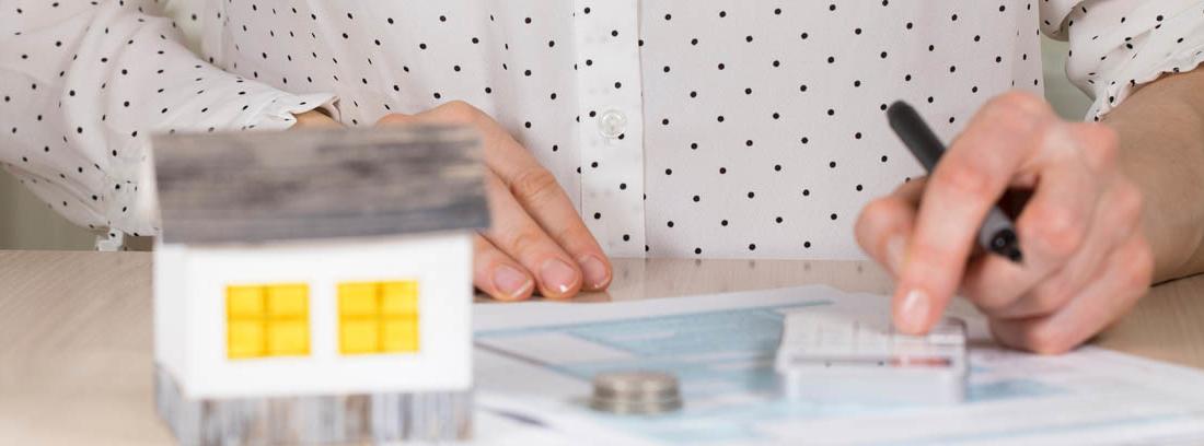 Vista parcial de mujer con boli, papeles y monedas, y maqueta de una casa