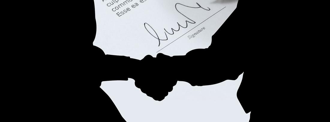 Siluetas en negro de dos personas estrechando la mano delante de mano firmando papel