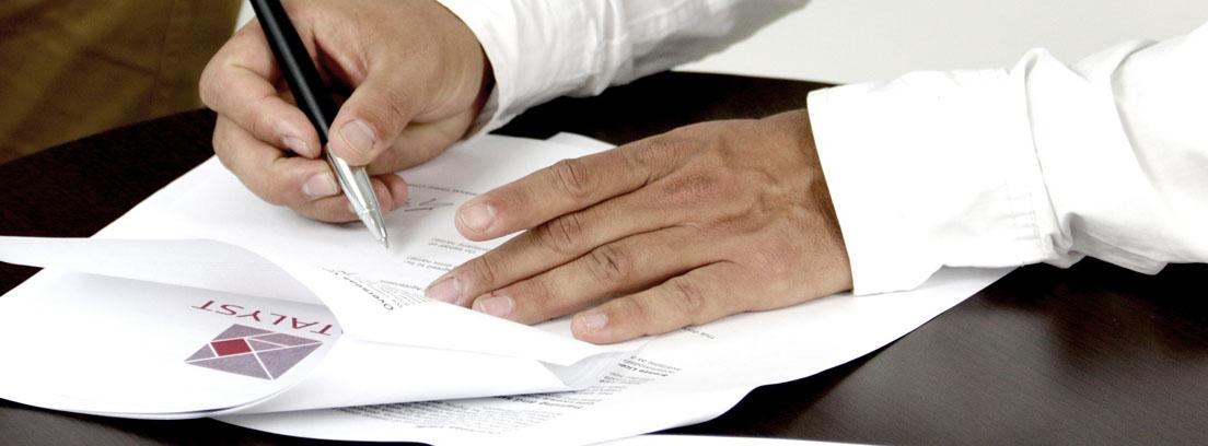 Dos manos sobre documentos en folios, una con bolígrafo