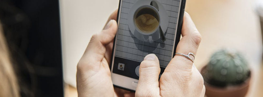 Manos sujetan un Smartphone en el que se ve una taza blanca con café