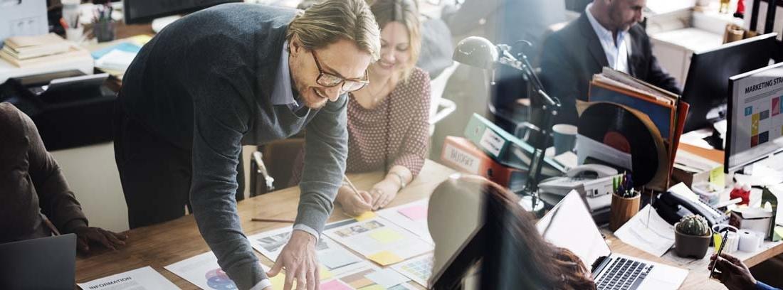 Un hombre señala los folios extendidos sobre una mesa y dos mujeres miran