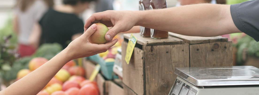 Mano extendida sobre un mostrador de fruta dando una fruta a otra mano