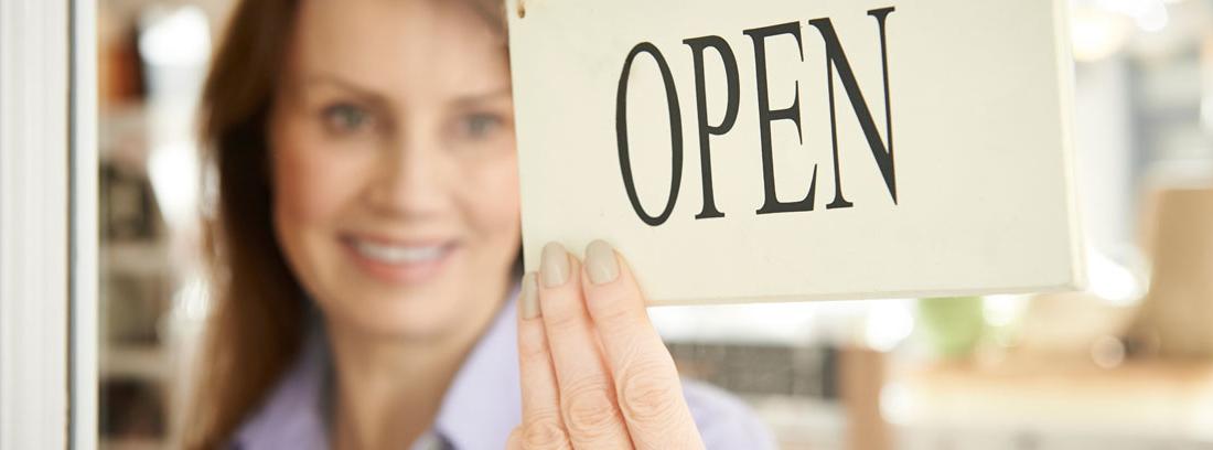 """Mujer sonriente girando un cartel en el que pone """"open"""" colgado en una puerta de cristal"""