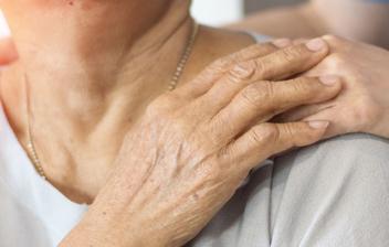 Mujer apoyando su mano sobre el hombro de otra mujer mayor sonriente