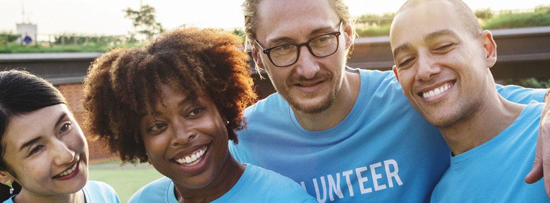Grupo de hombres y mujeres de voluntariado con camisetas azules en las que puede leerse la palabra Volunteer