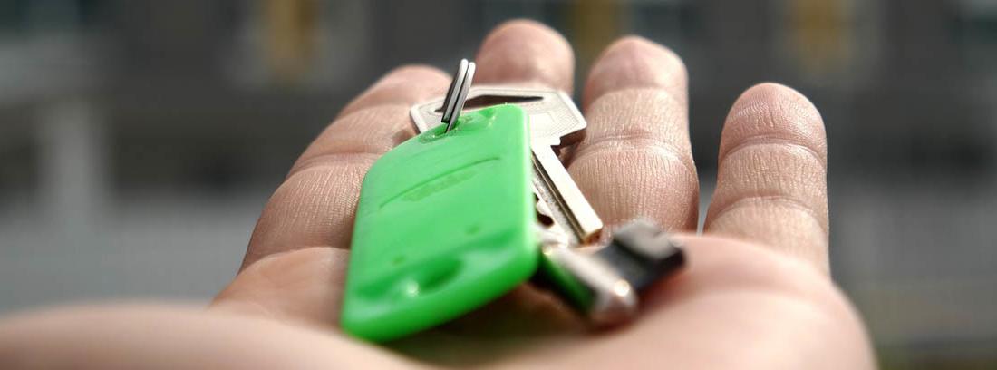 Persona con unas llaves color verde en la mano