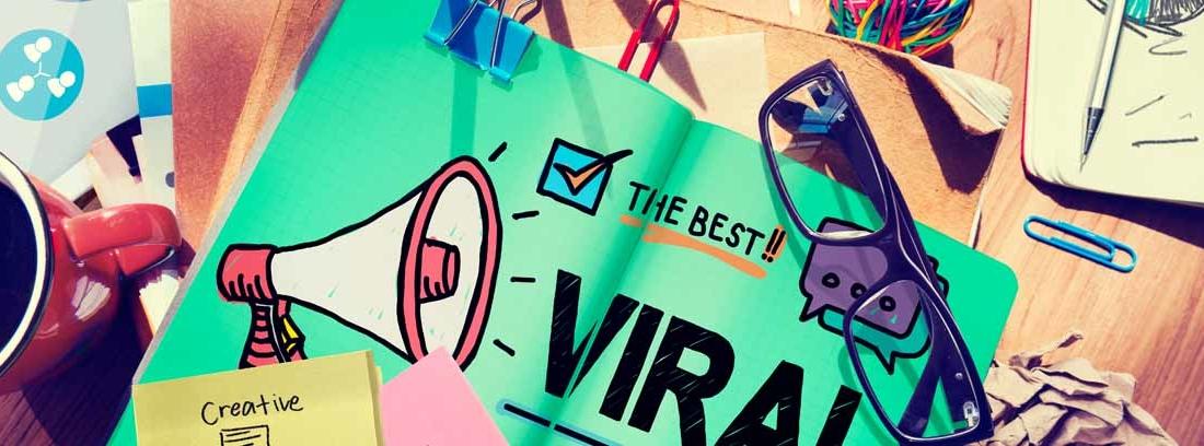 Mesa con papeles, gafas y un cuaderno con la palabra 'viral' escrito en él
