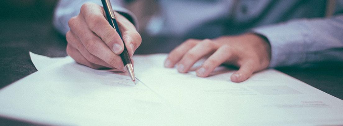 Mano firmando unos papeles