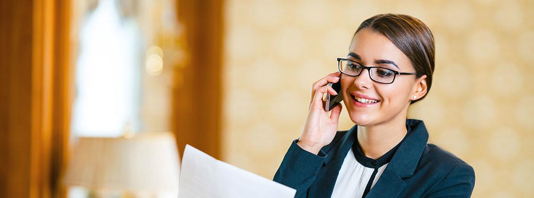 Mujer joven con traje habla por teléfono mientras sostiene unos folios