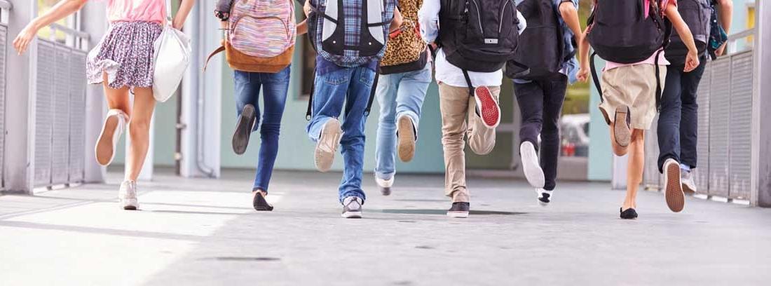Grupo de niños de espaldas corre con sus mochilas