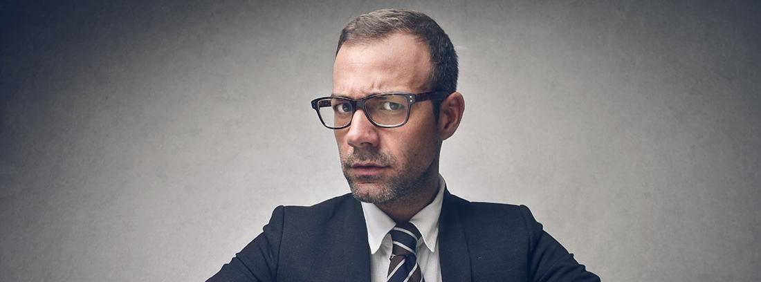 Hombre trajeado sentado en una mesa mirando inquisitivamente