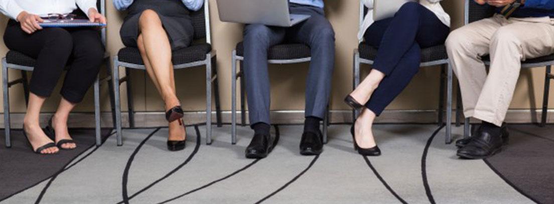 Pies de varios candidatos sentados en sillas