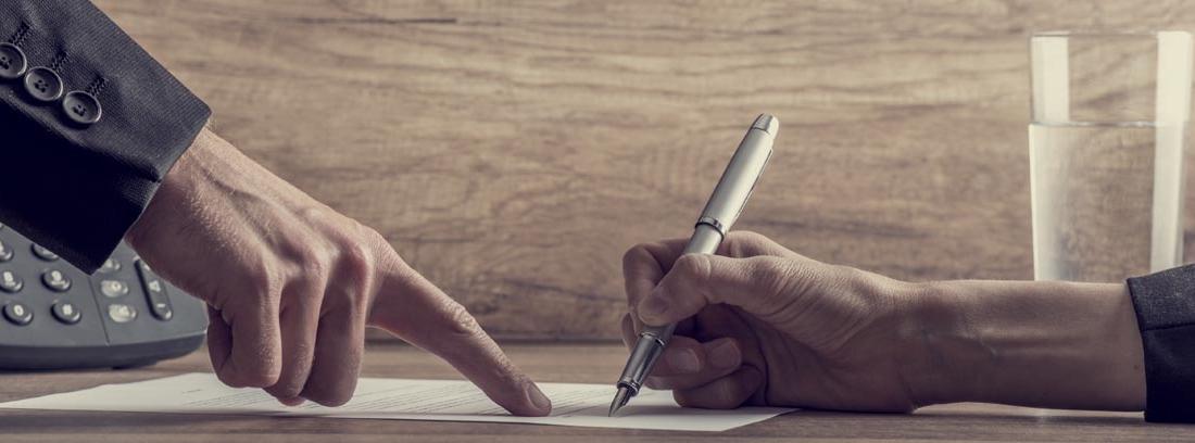Persona firmando la devolución de la cláusula suelo