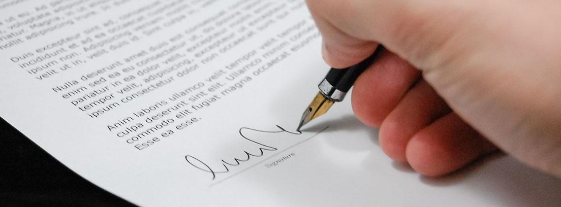 Mano con bolígrafo firmando en un papel escrito