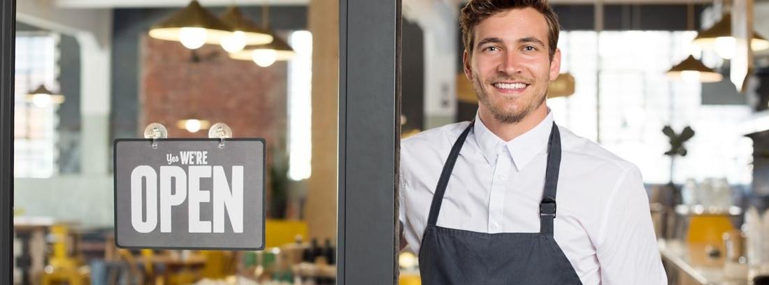 """Hombre sonriente con delantal junto a la puerta de un restaurante con un cartel en el que pone """"open"""""""