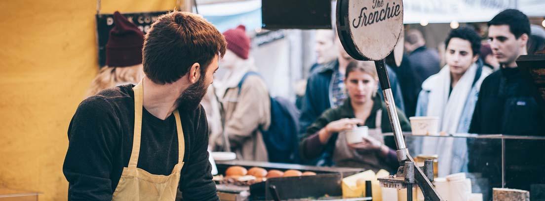 Hombre con delantal detrás de un mostrador