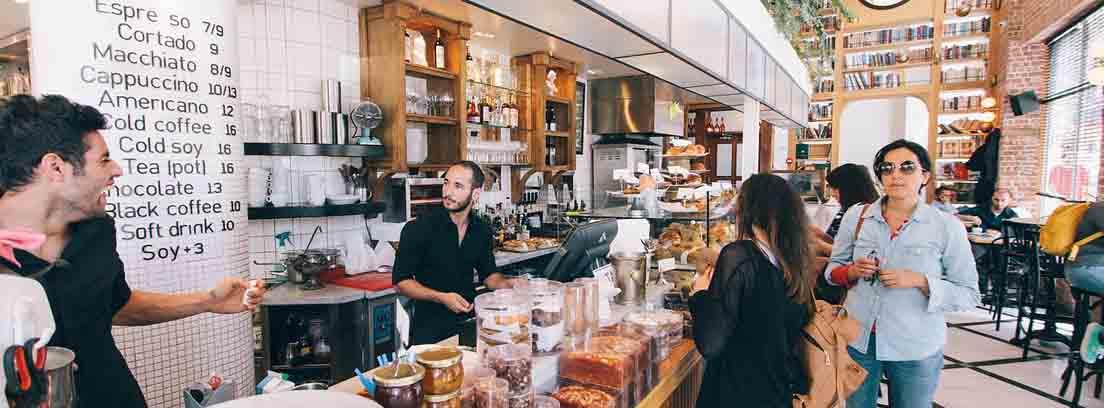 Barra de cafetería llena de productos con clientes a una lado y empleados al otro