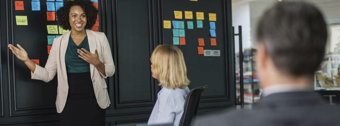 Mujer sonriente delante de pared negra con notas de colores y dos personas mirándola
