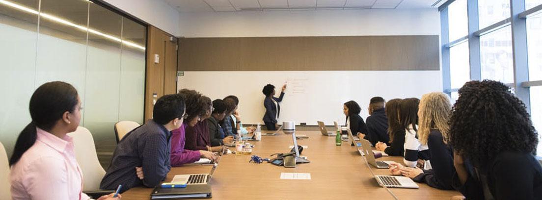 Gran mesa con personas sentadas a ambos lados con portátiles y mirando hacia el fondo