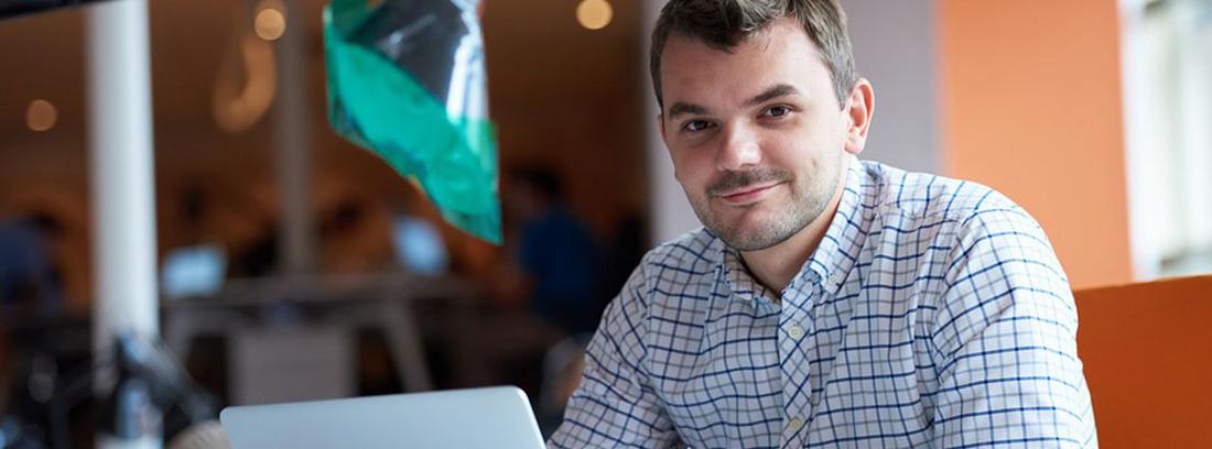 Hombre con camisa de cuadros sentado delante de un ordenador portátil abierto