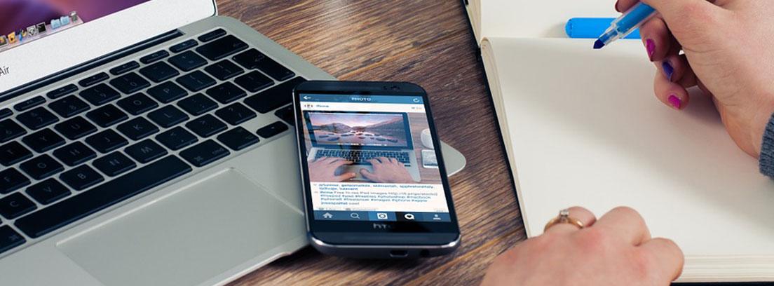 Sobre mesa ordenador portaril abierto, móvil y cuaderno con mano con boli azul