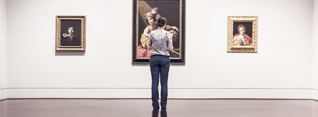 Mujer delante de tres cuadros colgados en pared blanca