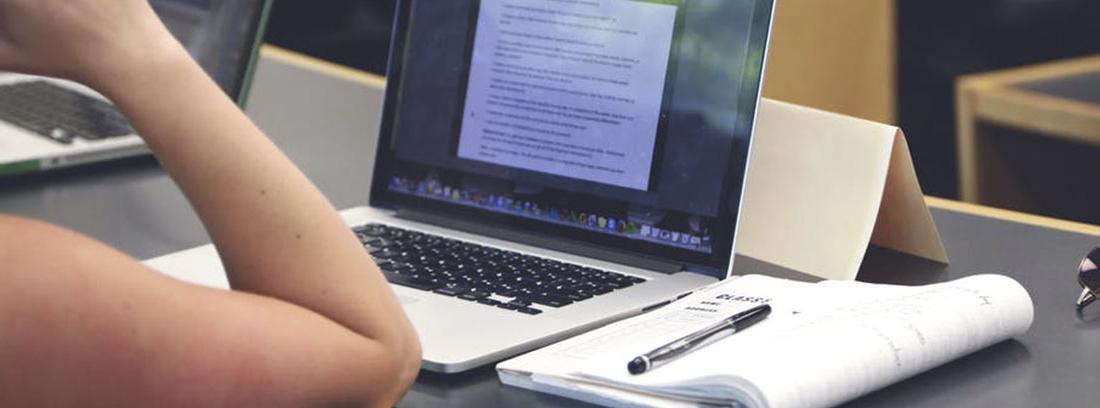 Mesa con portátil abierto, cuaderno con boli y codo de brazo apoyado