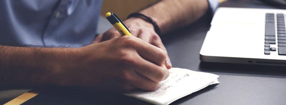 Mesa negra sobre la que escribe una mano con boli amarillo sobre hojas blancas