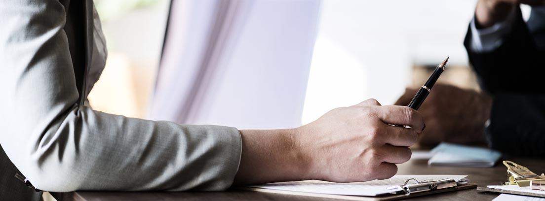 Primer plano de un brazo sujetando un boli sobre una mesa con papeles