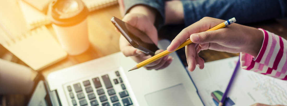 Dos personas trabajando con un ordenador portátil y un teléfono móvil