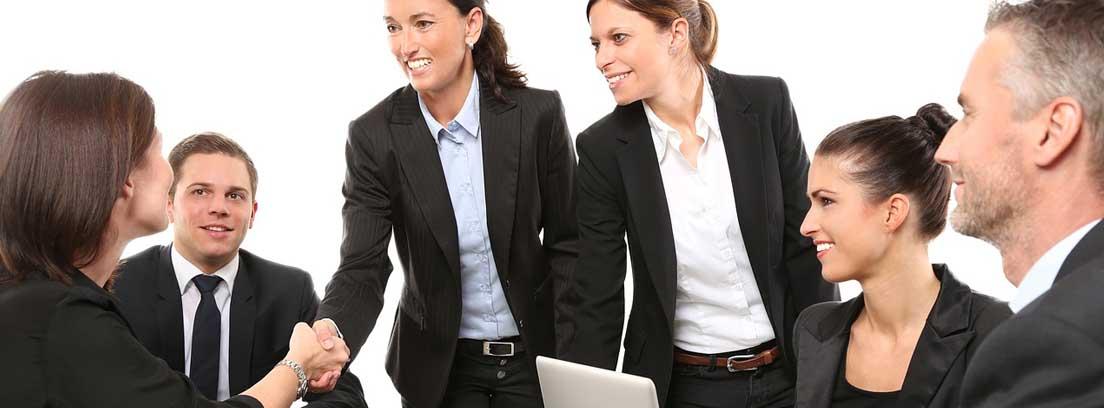Una mujer de pie tiende la mano a otra sentada tras una mesa