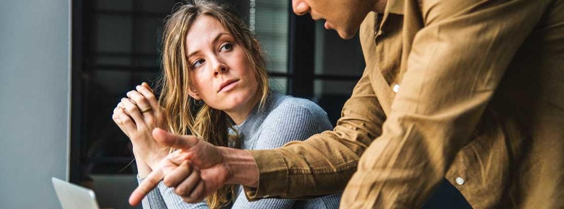Mujer sentada mira hacia hombre de pie que señala la pantalla de un portátil